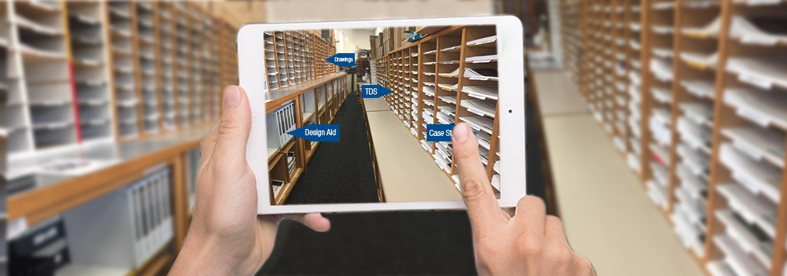 Photo of hands holding an iPad in a library of documents