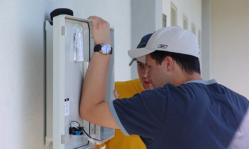 Photo of electrical staff evaluating a control panel