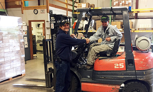 Photo of shipping and logistics personnel using a forklift